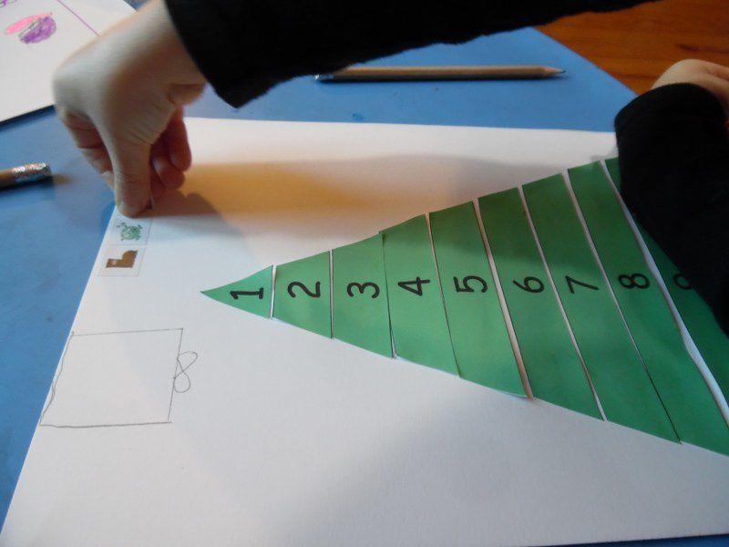 """Coller des bandelettes de papier de 10 à 1, pour fabriquer un sapin, écrire """"Bonne année"""" avec les Alphas, et décorer sa carte de jolis dessins et de boules de Noël."""