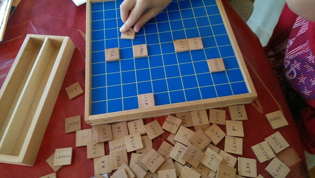 Lucas remplit le tableau de 100 en chiffres romains.
