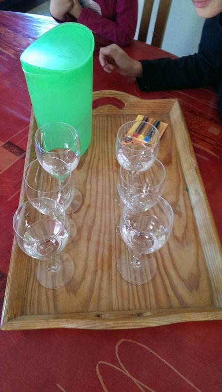 Nous avons pris six verres que nous avons alignés trois par trois. Nous avons mis de l'eau dans les verres de gauche et de droite, puis du colorant bleu dans un des verres et du colorant jaune dans l'autre verre. Nous avons mis aussi du bleu et du rouge dans les autres verres. Pas d'eau ni de colorant dans les verres du milieu.