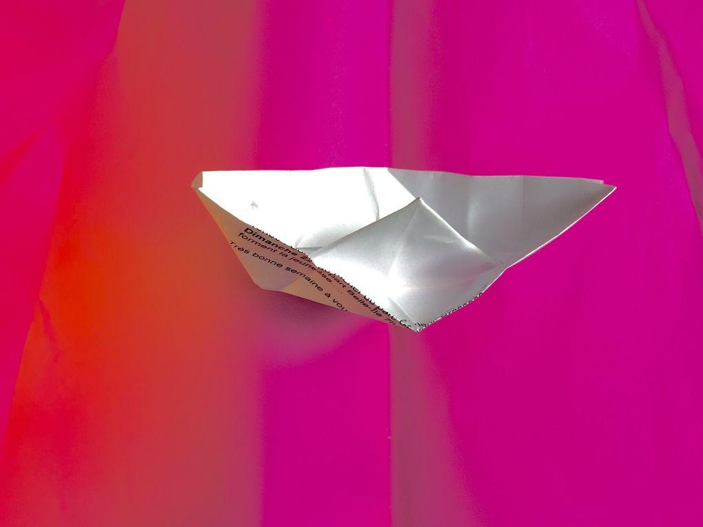 Bateau papier plié sur mer de papier, rose.