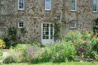 Une façade de maison de pays, couverte de fleurs, là poussent dans un joyeux fouillis, rosiers grimpants, clématites et vivaces accolés au mur.