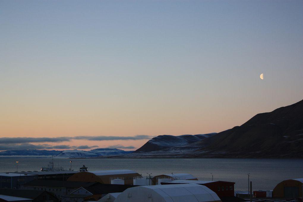 La vue de la fenêtre du salon en direction de l'Adventdalen et de l'Isfjord avec la Lune qui ne se couche pas/plus