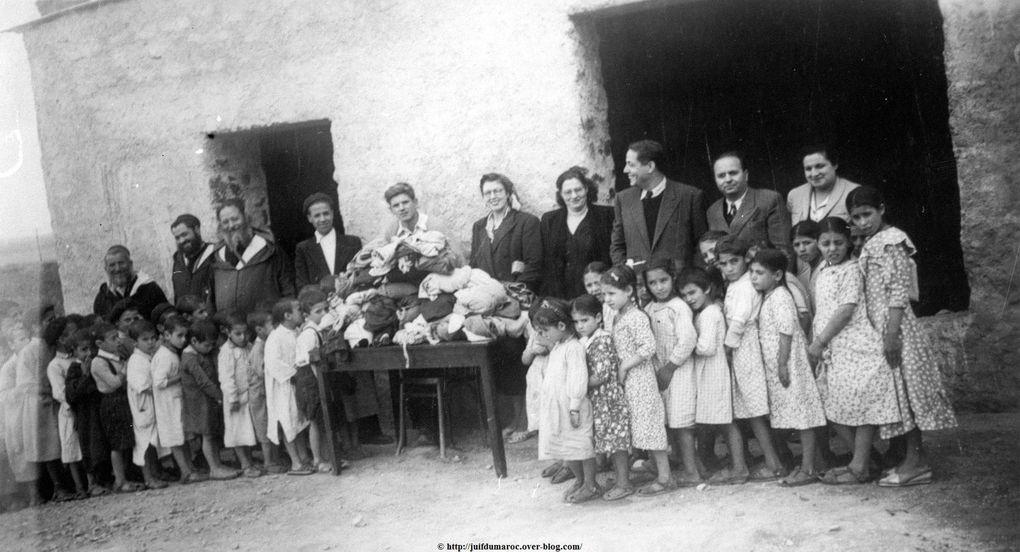 Distribution de vêtements aux élèves de l'École de Sidi Rahal 1949. Derrière les tables, de droite à gauche : Mme et M. Goldenberg, M. Elkaïm, de la Communauté israélite de Marrakech, la présidente de l'œuvre d'habillement, Mme Harrus, l'instituteur, puis les membres de la Communauté de Sidi Rahal. Devant, les élèves de l'école.