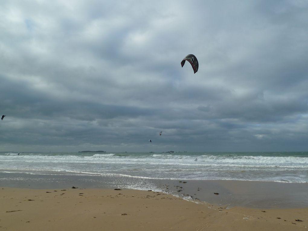 Quelques courageux surfent sur les vagues aidés par une aile type parapente..