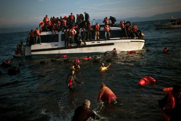 Des migrants secourus par des habitants après le naufrage de leur embarcation le 20 avril 2015 au large de Rhodes en Grèce ( EUROKINISSI/AFP/Archives / ARGIRIS MANTIKOS ) - Des migrants quittent leur bateau en train de sombrer le 30 octobre 2015 sur le rivage de l'île de Lesbos en Grèce ( AFP/Archives / CHRISTOFILOPOULOS )