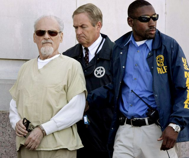 FILE – In this July 23, 2009, file photo, Tony Alamo, left, is escorted to a waiting police car outside the federal courthouse in Texarkana, Ark. Alamo, a one-time street preacher whose apocalyptic ministry grew into a multimillion-dollar network of businesses and property before he was convicted in Arkansas of sexually abusing girls he considered his wives, died in prison Tuesday, May 2, 2017. He was 82. (AP Photo/Danny Johnston, File)