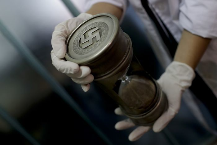 A Nazi medical device used to measure head size is seen at the Interpol headquarters in Buenos Aires, Argentina, Friday, June 16, 2017. - A member of the federal police holds an hourglass with Nazi markings at the Interpol headquarters in Buenos Aires, Argentina, Friday, June 16, 2017