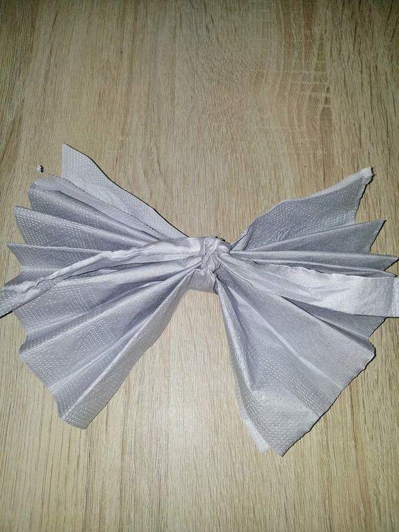 4ème étape: Faites un noeud avec la bandelette autour de l'accordéon en papier, positionnez le noeud sur les plis de la serviette et non sur la partie plate. Attention à réaliser cette étape délicatement de manière à ne pas casser la bandelette.