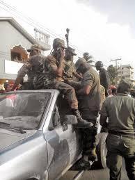 1-Exécution publique de Numa et Drouin. 2- Guy Phillipe et ses aimables compagnons d'armes. 3- Ex-militaires paradant dans Port-au- Prince