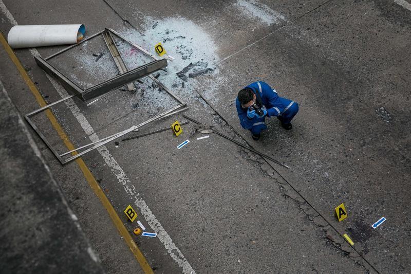 Venezolanos protestan mientras Trabajadores del Ministerio Público realizan hoy, jueves 8 de junio de 2017, el levantamiento planimétrico en el lugar en el que un joven de 17 años murió durante una protesta opositora, en Caracas (Venezuela). EFE