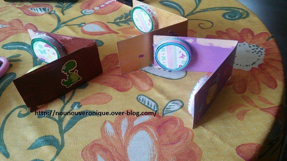 découper une bande de 24 cm de long sur 6 cm de large si vous utiliser des bouchon de petits pots (adapté les dimensions aux bouchons ou capsules) . Faire peindre le carton par l'enfant. décorer les bouchons ou capsules avec du papier à motif. Coller les bouchons sur le carton avec la colle à chaud. Faire décorer les castagnettes avec des gommettes puis vernir le tout.