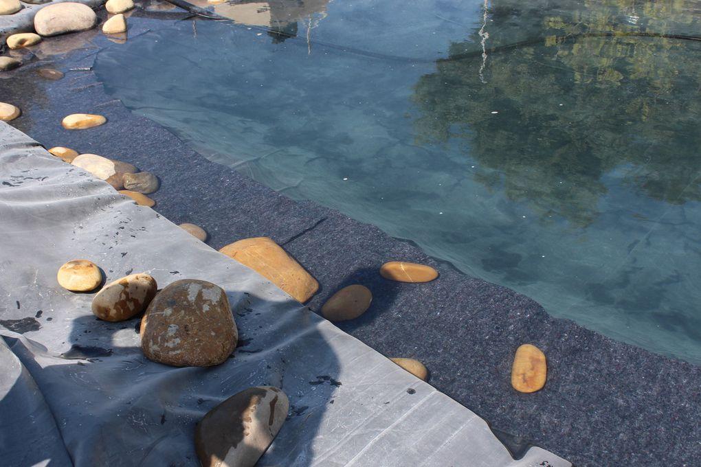 Habillage des berges avec les galets roulés....le soleil et les pieds dans l'eau ..le bassin commence à prendre forme