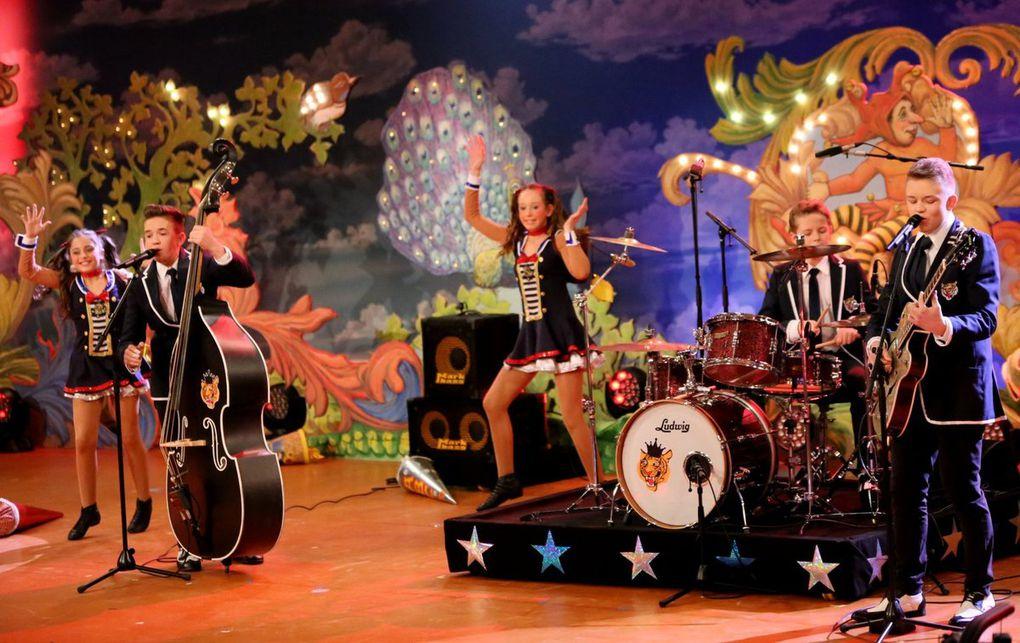 """Die """"Kusängs""""  Toni und Ludwig Hoßmann sowie Albert Hartmann aus Eußenheim, Lkr. Main-Spessart, mit einem Altersdurchschnitt von vierzehn Jahren, sangen sich mit ihrem """"Rock'n'Roll"""" in die Gunst der Zuhörer. Die Jungmusiker, – das zeigt der Bandname – sind auch im echten Leben Cousins. Sie überzeugten durch ihren jungenhaften Charme und sorgten mit ihrer fetzigen Musik und den dazu tanzenden Mädchen von der Tanzsportgarde Veitshöchheim und dann auch im  Finale mit """"Come on everybody"""" für eine tolle Stimmung im Saal."""