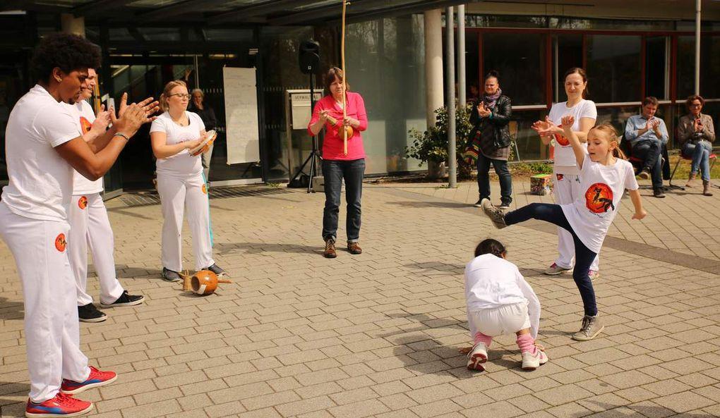 """Eine Augenweide und für die meisten Besucher Neuland waren auch die brasilianische Capoeira und der Breakdance, den der Brasilianer Jonathan Gabiru Brandao mit seiner Gruppe """"Brasa Brasil aus dem Salon 77 im Würzburger Frauenland aufführte. Mit seiner Erwachsenen-Kinder-Gruppe führte er anschaulich vor Augen, dass die von ihm praktizierte moderne Capoeira-Regional Spiel, Kampf und Tanz zugleich ist. Neben den verschiedenen Bewegungsabläufen brachte die Gruppe auch die brasilianischen und afrikanischen Lieder der Capoeira und die begleitende Musik auf Trommel, Pandeiro und Berimbau zu Gehör. Ihr Ursprung wird auf den afrikanischen Zebratanz zurückgeführt, der während der Kolonialzeit von verschleppten Sklaven praktiziert und weiterentwickelt wurde. Während der 1970er Jahre  entwickelten sich auch viele der heute charakteristischen Akrobatiken, wie hohe, gedrehte Sprünge oder Salti."""