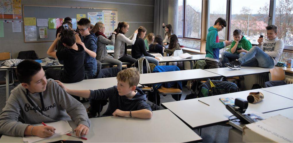 """Mannequin-Challenge, der Mitmach-Trend aus den USA, bei dem eingefrorene Gruppenszenen, das """"Feeze"""", per Video gefilmt und mit passender Musik kombiniert werden, hat inzwischen auch Deutschland erfasst  - den privaten Freundeskreis ebenso wie das prominente Fußballteam. Und so hatten auch die Schüler der 7. Jahrgangsstufe sichtlich Spaß daran, positive wie auch negative Erfahrungen aus dem Schulalltag beim Mannequin-Challenge zum Ausdruck zu bringen. """"Ein Horrorszenario einerseits und der Wunschtraum eines jeden Lehrers und Erziehungsberechtigten"""" So ließen sich die beiden kurzen Filmclips betiteln, die Klassenleiter Stefan Reitzenstein zum Abschluss der Veranstaltung in der Aula präsentierte, wie Klassen ihren Schulalltag, zum Teil chaotisch,  in ein statisches Bild umsetzten."""