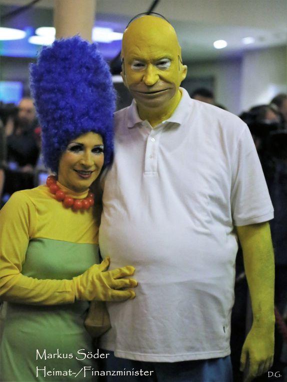 """Sehr aufwändig war auch wieder das Kostüm von Finanzminister Markus Söder (CSU): Er kam mit hoher quietschgelber Glatze als Comicfigur Homer Simpson als Hommage auf die normalen Leute. Söder: """"Homer Simpson würde CSU wählen"""", hatte er schon im Vorfeld der Deutschen Presse-Agentur gesagt. Seine Frau Karin kam passend dazu mit gigantischer blauer Turmfrisur als Homers Ehefrau Marge Simpson. Und was die Politik von Simpson lernen könnte: """"Vor allem Gelassenheit."""""""