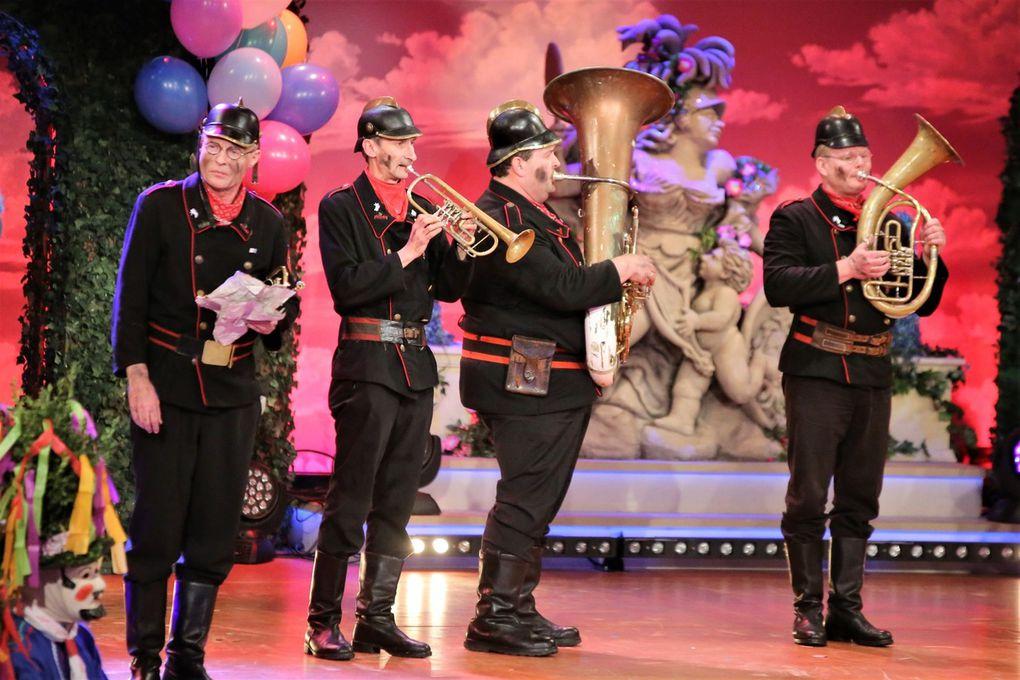 """Die Altneihauser Feierwehrkapell'n sind für viele auch heuer wieder ein Höhepunkt des Abends. Ihr """"Anführer"""" und """"Spiritus rector"""" Norbert Neugirg, seit Erfindung der Altneihauser im Jahre 1985 Kommandant, lief wieder mit seinen provokanten Reimen zur Hochform auf, während seine Mannen seine skurrilen Ideen auf der Bühne umsetzten, vom Narrenvölk umjubelt.  Neugirg legt los mit:  """"Auf Anraten der Krankenkassen haben wir die Oberpfalz verlassen. Denn bei uns daheim grassieren die Grippe und die Noroviren. Das brachte uns auf den Gedanken: das kleinere Übel, das ist Franken."""" Starker Tobak ist auch: """"Franken dick und drall, ein versoff'ner Saal, und wir sind so dumm und kommen jedes Mal."""" und: """"Möbelbeize Frankenwein."""" Weiter reimte er auf die Franken:  """"Der Schöpfer schuf den Frankenschlag - und er hatte einen schlechten Tag"""" oder: """"Söder voller gelber Stellen, ich tipp auf Bayern-Ei und Salmonellen"""" und eine Bauernregel:  """"Steht die Sau auf einem Bein, wird sie wohl beim Metzger sein"""".   Auch für die Altneihauser Feierwehrkapell'n gibt es Standing Ovation, als sie sich verabschiedet mit: """"Thanks for watching this fucking show! Oberpfalz first and hou hou hou!"""""""