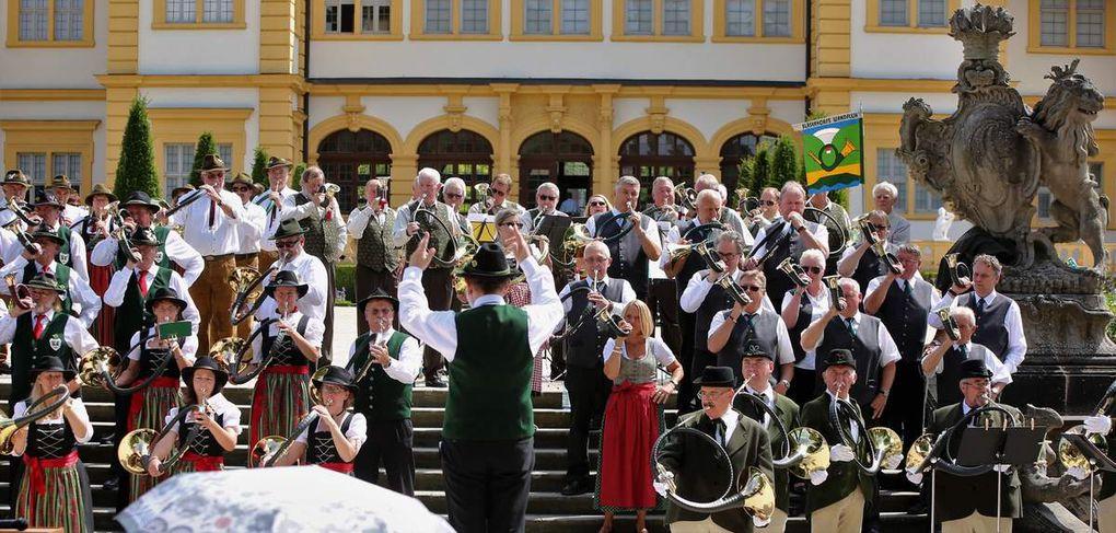 """Ein imposantes Bild bot sich heute Hunderten von Zuhörern im Veitshöchheimer Hofgarten vor der Schlosskulisse, als fünf Bläsergruppen gemeinsam zu Beginn """"Willkommen"""", zwischendurch """"Auf, auf zum fröhlichen Jagen"""" und am Ende """"Auf Wiedersehen"""" aus über 50 Hörnern erschallen ließen. Nur die Marktheidenfelder Bläser mit ihren Es-Ton-Hörnern konnten diese Stücke nicht mitspielen."""