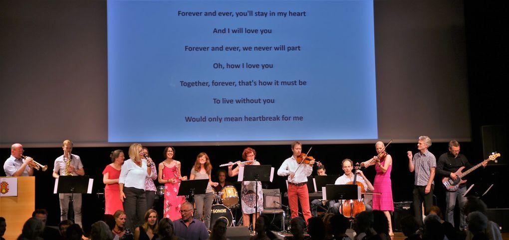 """Zum rauschenden Finale versammelten sich wie zu Beginn alle Lehrkräfte mit ihren Instrumenten auf der Bühne und davor der Projektchor um gemeinsam mit dem Publikum Dorothea Völker mit Demis Roussos Hit """"Forever and ever"""" zu huldigen."""