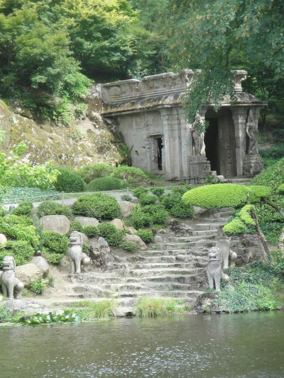 """On devine la pagode entre les arbres, puis l'embarcadère puis à nouveau la pagode qui se dévoile, de superbes reflets, des arbres bluffants, le temple kmer et son bouddha, les lions montant la garde le long de l'escalier montant au temple,les poissons qui """"accourent"""" en quête d'une possible nourriture, un joli pont japonais, un autre européen et enfin la Corne du Naja, recouverte de losanges de verre doré qui était posée à l'extrémité de la toiture d'un temple thaïlandais, elle symbolise l'esprit protecteur des eaux."""