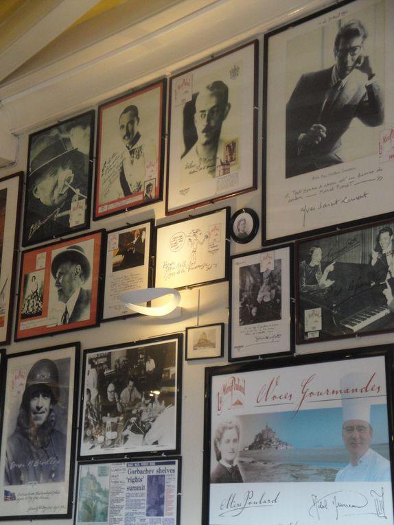 La cuisine de la Mère Poulard, là où l'on prépare la fameuse omelette, une vue sur la salle à manger, au mur les photos des célébrités qui ont fréquenté le lieu, puis maisons, rues et enseignes.