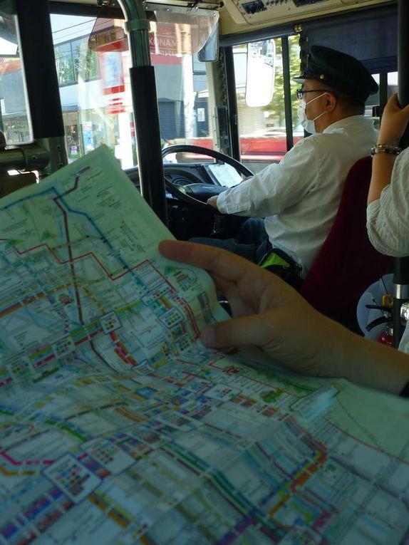 """quelques photos de vie quotidienne, et surtout de transport : un soit disant restaurant français...hmhm... un """"petit immeuble"""" en construction, les horaires du comptoir de nuit de la poste (car oui, ici, la poste est ouverte 24h/24 !), les espaces pour vélo et les piétons dans la rue (chacun à sa place !), un parking de voiture à étage (avec ascenseur à voiture bien sûr), le fameux shinkansen (TGV), un autre train plus classique, et dans le bus à Kyoto"""