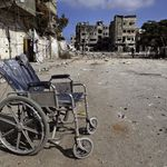 A wheelchair lies abandoned on a debris-strewn street amid the rubble of houses damaged by Israeli strikes