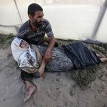 Palestinian man holds his mother, who was wounded in an Israeli air strike