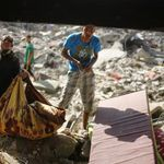 Palestinians remove their belongings from their destroyed house in the Shejaia