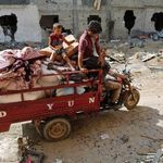 A Palestinian family salvages belongings from the ruins of buildings destroyed by Israeli air strikes