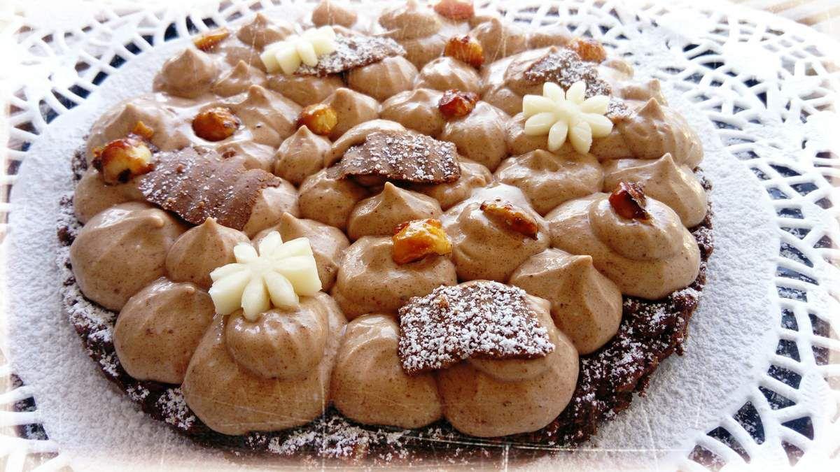 recette pour 6 personnes amateurs du goût de la noisette : 1) préparez le croustillant chocolat (le fond de la tarte) émiettez 120 g de sablés bretons + ajoutez 30 g de noisettes trorréfiés concassées + 30 g de grains de riz soufflés au chocolat (coco pops) + 45 g de chocolat noir et au lait fondu + 10 g d'huile , tapissez le fond de votre cercle taille 18 cm 2) faire prendre au frais (pas de cuisson c'est top non ??) 3) préparez votre ganache gianduja  avec 200 g de crème liquide + 100 g de gianduja , faire bouillir la crème et ajoutez hors du feu le gianduja , laissez cette crème au frigo au moins 12h 4) versez la crème au robot avec le batteur , montez celle ci en chantilly 5) garnissez votre fond de tarte croustillante 6) décorez avec des copeaux de votre chocolat gianduja (recette sur le blog) et des noisettes caramélisées