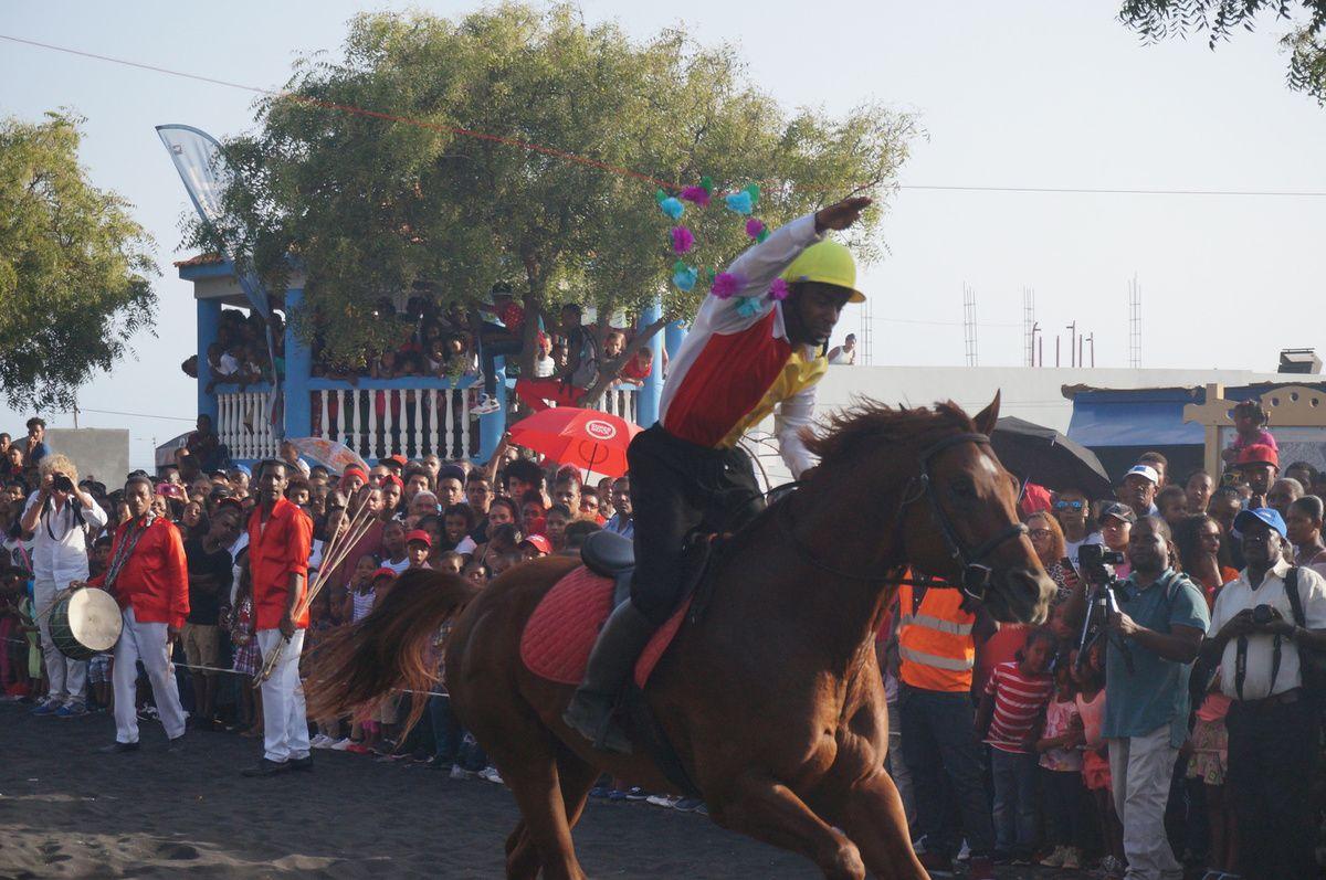 L'île de Fogo est un volcan actif qui culmine à 2829 mètres. L'île est très escarpée, car de petite superficie. La ville principale est Sao Filipe, et chaque premier mai s'y déroule une grande fête traditionnelle. Plusieurs jours en amont se déroulent un tas de festivités, centrées autour de quelques chevaux élevés sur l'île. Courses entre chevaux, tournois sportifs, animations musicales... Beaucoup d'expatriés aux Etats Unis rentrent à l'occasion de cette fête. Car Fogo et Brava, les deux îles le plus au Sud-ouest de l'archipel, ont connu une plus forte émigration vers l'Amérique, due aux embarcations sur les baleiniers. On a pu apprécier les différences entre le créole de Santiago, et le créole de Fogo, plus anglicisé &#x3B; les habitants préférant nous parler en anglais, ce qui arrive rarement sur Santiago ! Quelques photos des courses de chevaux, de la bandeira, au cours de laquelle les cavaliers tentent d'attraper des couronnes de fleurs. Photos également de Sao Filipe, aux petits quartiers étagés, délimités par de petites places. Une des constructions typiques de Fogo et de son histoire coloniale sont les sobrados, maison coloniale colorée de deux étages, avec en façade un balcon de bois.