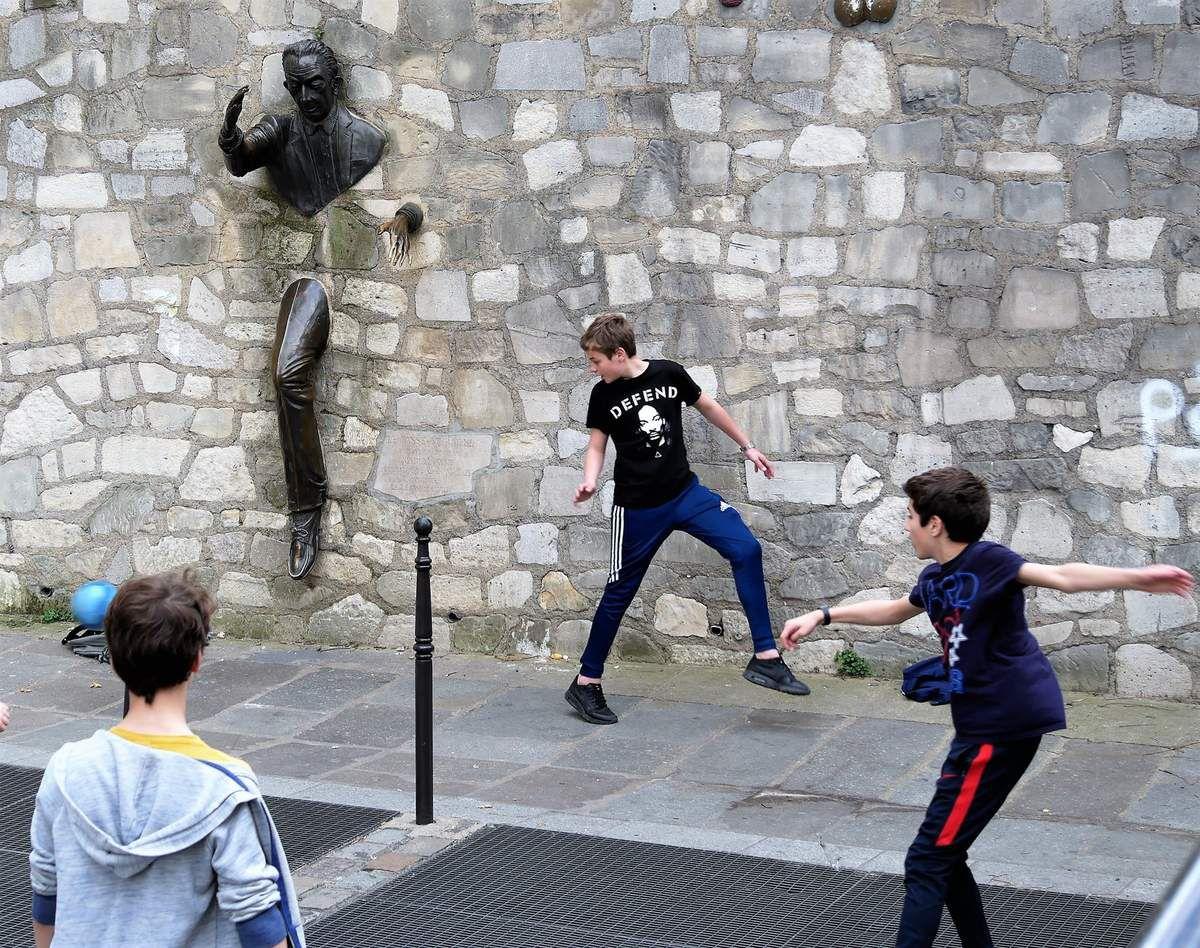 Place Marcel Aymé. 28 mars. 15H. Le passe-muraille et les footballeurs.