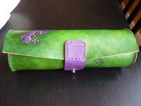 Trousse fermeture bouton de col. Motif lézard avec empruntes couleur violet et vert.