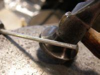 Le tube que j'arrondis au marteau&#x3B; puis que je taraude. Le fil carre que j'arrondis...