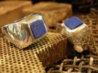 Deux lapis scies et polis une face&#x3B; les pierres en cours d'ajustage dans les chevalieres&#x3B; les deux bijoux finis.