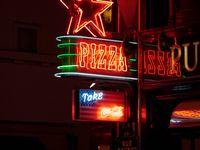 """Dans l'ordre, l'Opéra Garnier, The American Dream, son enseigne Pizza, l'Olympia, le chausseur Weston, qui comme son nom l'indique est bien français, une colonne Morris, l'église de la Madeleine, la perspective de l'obélisque de la Concorde Assemblée Nationale et, dans le fond mais très rapproché par le téléobjectif, le dôme doré des Invalides, une façade très """"années 50"""" et enfin le Harry's Bar qui excelle à donner les prévisions aux élections du président US"""