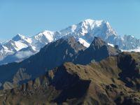 Le Crêt du Rey est visible de loin, caractéristique avec son arête sud découpée. Le sentier monte par le nord-est. Derrière, le Mont Blanc domine le paysage.