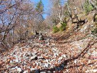 Un chemin rocailleux le long de la barre rocheuse où grimpe un alpiniste.
