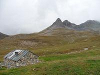 Des bornes tricolores délimitent le parc de la Vanoise. Sur une crête, un chamois. Le chalet et l'aiguille des Aimes.