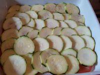 Dans un plat du four, versez un filet d'huile d'olive, mettez une rangée de rondelle de tomate  puis une rangée de rondelles de courgettes