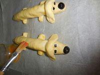 2 - Aplatir et modeler chaque extrémité du corps. Dans les restants de pâte, façonner des petits boudins aplatis sur chaque bout, à placer sur la tête du chien (soudés avec un peu d'eau) pour matérialiser les oreilles. Faire de même pour positionner les pattes sous le corps du chien en arrondissant les extrémités. Faire de petites boules de pâtes pour les yeux sur lesquelles seront déposés des morceaux d'olives noires, et finir en plaçant l'extrémité d'une olive noire au bout du museau du chien pour dessiner sa truffe. Badigeonner l'ensemble de la figurine au jaune d'oeuf et mettre à cuire au four th 6/7 pendant 10 mn environ. La pâte doit être gonflée et dorée.Servir aussitôt, accompagné de frites et d'une salade