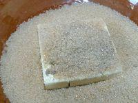4 - Passer à la préparation du crumble. Dans un récipient, mélanger le beurre froid, le sucre roux, le sucre vanillé, la farine, la cannelle et la noix de coco. Malaxer du bout des doigts pour obtenir un sable grossier.