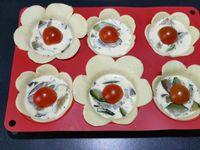 4 - Déposer les corolles de pâte dans un moule à muffins en silicone comme sur la photo. Bien tasser dans le fond et faire épouser la pâte aux parois du moule. Remplir chaque bouchée de petits morceaux de tomate, rajouter les courgettes-aubergines-échalote, et verser la préparation oeuf-crème fraîche. Terminer en déposant une demi-tomate cerise. Découper avec un emporte-pièce plus réduit des petites fleurs dans la pâte restante pour la décoration. Mettre au four th 6,5/7 (200°) pour 15 mn environ pour les bouchées, surveiller la cuisson pour retirer les petites fleurs avant dès qu'elles sont gonflées et dorées.