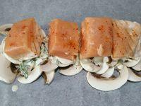 """3 - Couper le 1/2 citron vert en fines rondelles. Recouvrir une plaque allant au four d'un grand rectangle de papier sulfurisé, disposer au centre les champignons émincés, puis arroser avec la préparation de sauce. Couper le pavé de saumon en 4 et placer les morceaux par dessus, poivrer, saler et saupoudrer de piment d'Espelette. Venir ajouter un peu d'aneth, et terminer par les rondelles de citron vert. Refermer les papillotes (voir technique de pliage dans l'article """"Papillotes de gambas p-d-terre au beurre d'herbes"""") et enfourner à th 7 pour 15 à 18 mn."""