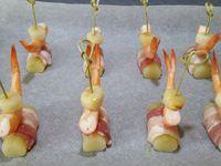 2 - Faire revenir les noix de pétoncles 1 à 2 mn dans une poêle avec un filet d'huile d'olive et réserver. Découper les tranches de lard de façon à ce qu'elles fassent bien le tour des cylindres de pommes de terre et les entourer autour de ces dernières. Prendre les piques en bambou, y enfiler les noix de pétoncles, les crevettes roses et venir piquer le tout sur les rouleaux de pommes de terre au lard. Faire fondre le beurre au micro-onde quelques secondes, le poivrer. Disposer vos amuse-bouches sur une plaque allant au four recouverte de papier sulfurisé et les badigeonner au pinceau de beurre fondu poivré. Placer la plaque au four en position grill pour environ 5 mn en surveillant.