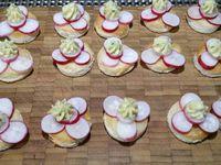 2 - Disposer sur chaque disque de pain de mie toasté 4 rondelles de radis, déposer sur le milieu un bonne noisette de beurre pommade à la poche à douille. Placer les toasts sur un plateau en décorant avec les queues de radis.