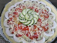 3 - Préchauffer le four th 6 (180°). Etaler la pâte et la placer dans un moule à tarte, décorer les bords à la fourchette et piquer le fond de la tarte pour éviter qu'elle ne se soulève. Verser l'appareil dans le fond de tarte, disposer harmonieusement dessus  de l'extérieur vers l'intérieur,  une rangée de rondelles d'aubergine, puis le chorizo, les tomates jaunes et rouges en les alterlant, disposer un cercle central de rondelles de courgettes et terminer par les lamelles de champignons sur les aubergines. Parsemer le tout de mozzarella râpée et si vous le souhaitez ajouter encore un peu de thym. Enfourner la tarte pour 40 à 45 mn environ th 6 (180°). Réduire éventuellement la température au bout de 30 mn et couvrir de papier aluminium si besoin en fin de cuisson pour que les légumes soient bien cuits mais que la pâte reste dorée sans brûler.