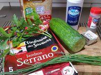 1 - Bien laver le concombre.  Le couper en fines lamelles dans le sens de la longueur. Couper également les tranches de jambon Serrano en lanières de la même largeur que le concombre. Ciseler la ciboulette fraîche et l'incorporer aux portions de carré frais. Saler et poivrer.