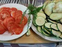 1 - Mettre le four à préchauffer th 6 (180°). Laver et sécher les tomates, l'aubergine et la courgette, les tailler en fines rondelles. Peler et couper la gousse d'ail en deux et en frotter l'intérieur d'un plat à gratin. Verser un fond d'huile d'olive dans le plat. Disposer successivement une couche de rondelles d'aubergine, saler, poivrer, arroser d'un filet d'huile d'olive et répartir un peu de parmesan râpé et de thym égrainé, puis faire de même avec les courgettes et les tomates, renouveler l'opération jusqu'à épuisement des légumes, répartir au final 3 ou 4 morceaux de feuille de laurier. Enfourner le tout pour 40 à 45 mn environ (suivant les fours) th 6 (180°) les légumes doivent être fondants. Servir dès la sortie du four..